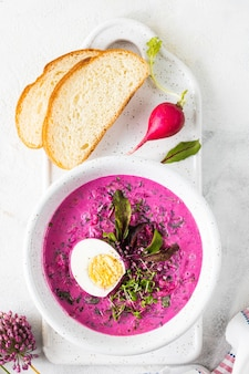 Zuppa estiva fredda di barbabietole, cetrioli e uova in un piatto bianco su un tavolo di pietra bianca. vista dall'alto. copia spazio.