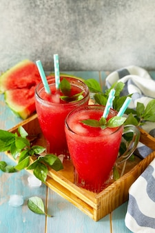 Smoothie freddo all'anguria bevanda estiva all'anguria in bicchieri e fette di anguria