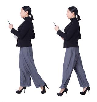 Collage a figura intera figura che cammina di 40s 50s asian lgbtqia + pantaloni e scarpe da donna con capelli neri. la femmina usa lo smartphone, il taccuino e cammina sul lato destro su sfondo bianco isolato