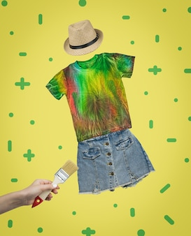 Un collage di una mano con un pennello e un set di vestiti con una maglietta color tie dye. arte contemporanea. collage.