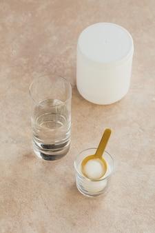 Polvere di collagene in una ciotola, bicchiere d'acqua e misurino su uno sfondo beige chiaro. assunzione di proteine extra. concetto di integratore naturale di bellezza e salute.