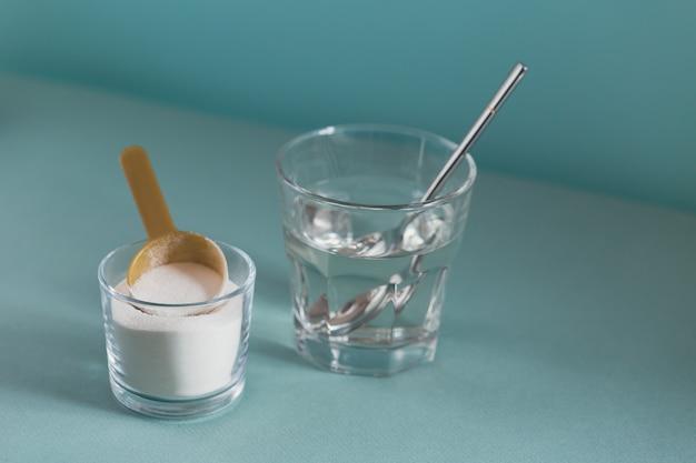 Polvere di collagene nella ciotola, bicchiere d'acqua e misurino su azzurro
