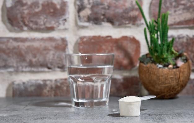 Polvere di proteine del collagene - idrolizzato, in un cucchiaio di legno sul tavolo di pietra, accanto al bicchiere d'acqua.