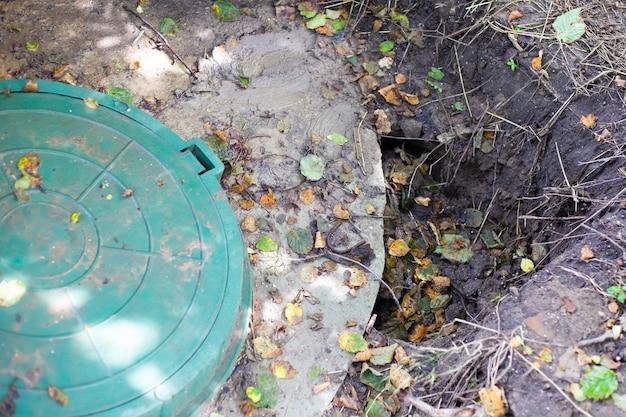 Terreno crollato vicino agli anelli di cemento di un pozzo sotterraneo. fossa settica installata, scarsa compattazione del suolo.