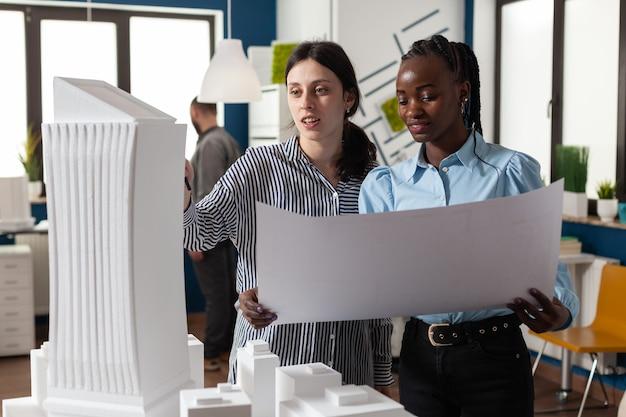 Colleghe architetti donne che controllano i piani di progettazione del layout dei modelli. team multietnico di lavoratori professionisti in piedi alla costruzione di un modello di maquette per un progetto tecnologico moderno