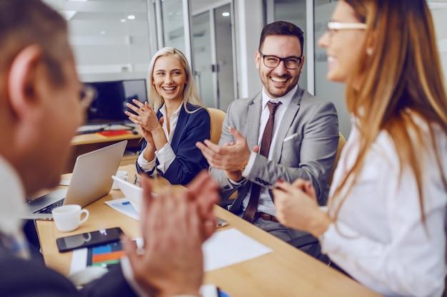 Colleghi che applaudono alla loro collega di sesso femminile per un'idea eccellente mentre erano seduti in sala riunioni.