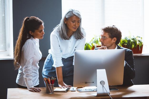 Colleghi che discutono di una nuova presentazione seduti in coworking room guardando il computer desktop