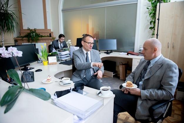 Colleghi che hanno una pausa caffè in ufficio alla scrivania