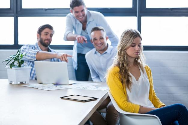 Colleghi che ridono della donna di affari in ufficio