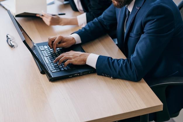 Colleghi seduti a una scrivania con un laptop professionisti della finanza di comunicazione