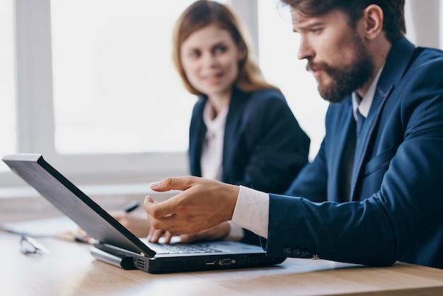 Colleghi seduti a una scrivania con un laptop funzionari di comunicazione
