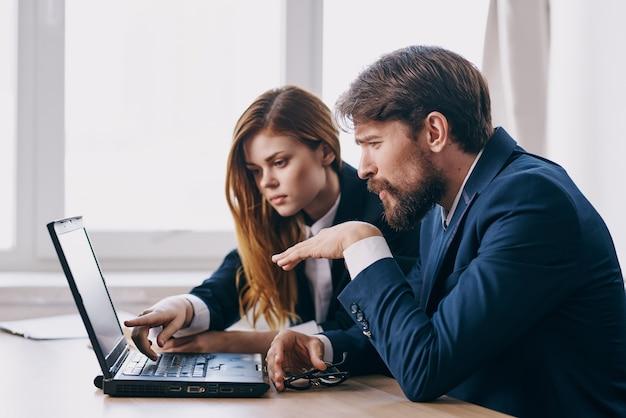 Colleghi seduti a una scrivania con un laptop professionisti della comunicazione