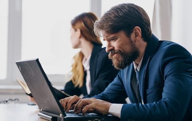 Colleghi in giacca e cravatta al team di tecnologia portatile scrivania da lavoro. foto di alta qualità