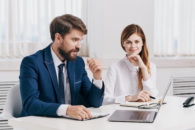 Colleghi che parlano al tavolo davanti alla tecnologia dei professionisti del laptop