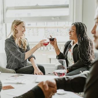 Colleghi che brindano bicchieri di vino al lavoro