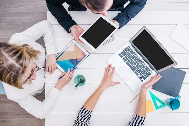 Colleghi che utilizzano i gadget alla scrivania
