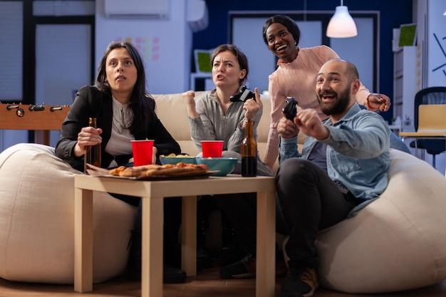 I colleghi di diversa etnia si divertono a stare insieme in ufficio dopo il lavoro giocando a console in tv. lavoratori multietnici che si divertono alla festa di celebrazione al chiuso
