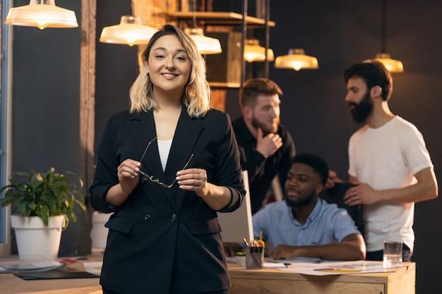 Colleghi che lavorano insieme in un ufficio moderno utilizzando dispositivi e gadget durante riunioni creative