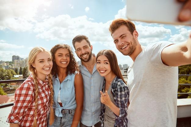 Collezionando momenti felici, un gruppo di giovani allegri e giovani sta facendo selfie e sorridendo