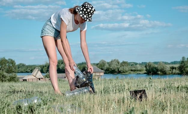 Raccolta di rifiuti di plastica. la ragazza raccoglie bottiglie di plastica. inquinamento ambientale.