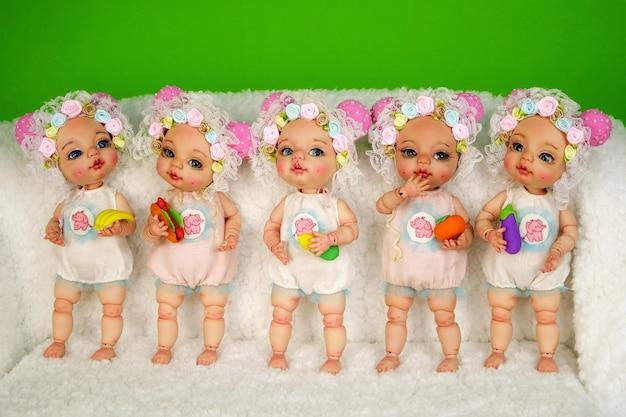 Collezione di adorabili bambole artigianali con snodi sferici che stanno in fila su una superficie bianca e ispida.
