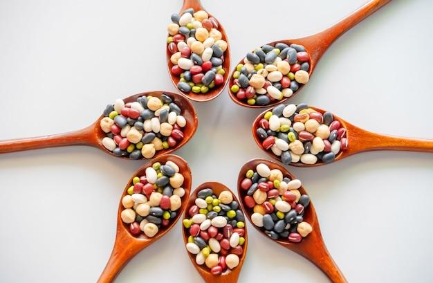 Raccolta di fagioli in cucchiai di legno.