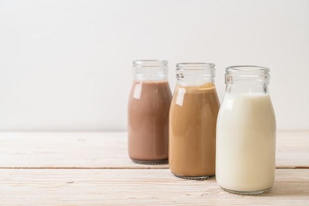 Raccolta di bevande al cioccolato al latte, caffè e latte fresco in bottiglia su legno