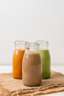 Raccolta di bevanda tè al latte tailandese, tè verde matcha latte e caffè in bottiglia su fondo di legno