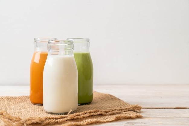 Raccolta di bevande tè al latte tailandese, tè verde matcha latte e latte fresco in bottiglia sulla tavola di legno