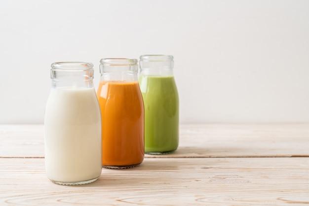 Raccolta di bevanda tè al latte tailandese, tè verde matcha latte e latte fresco in bottiglia sulla tavola di legno