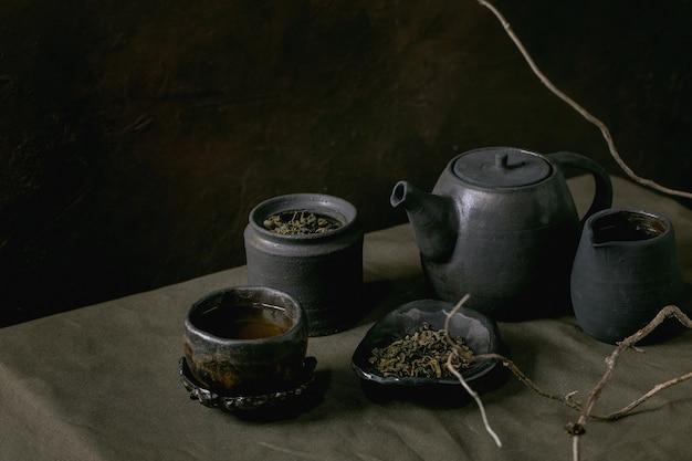 Collezione di teiera artigianale in ceramica nera fatta a mano, bollitore, brocca, barattolo, tazza wabi sabi, piattino per la cerimonia del tè in piedi su tovaglia di lino con ramo secco in camera oscura.