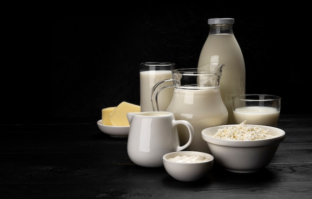 Raccolta di prodotti lattiero-caseari su fondo di legno nero con lo spazio della copia