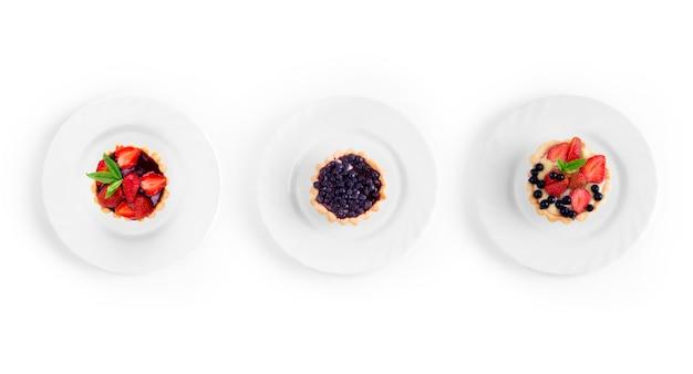 Raccolta di dessert con fragole e ribes su un piatto su sfondo bianco