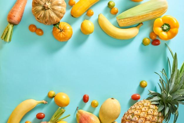 Raccolta di frutta e verdura gialla fresca su sfondo azzurro