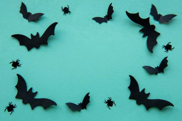 Raccolta di oggetti per feste di halloween che formano una cornice, pipistrelli neri e ragni su sfondo verde