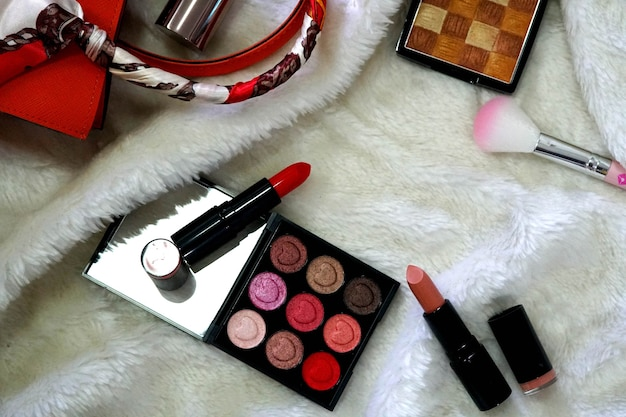 Collezione trucco set ombretto colorato fard rossetto e cipria su un panno di visone bianco