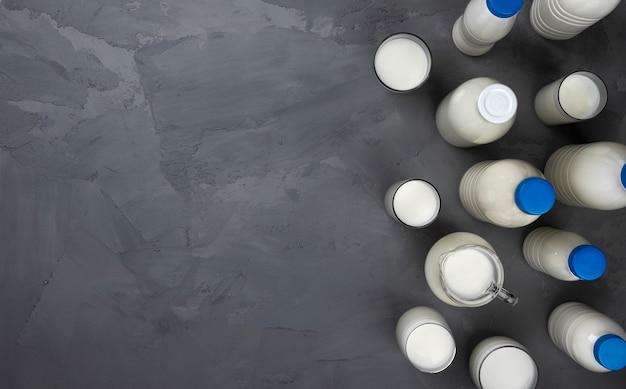 Collezione di bottiglie di latte su pietra grigia, vista dall'alto