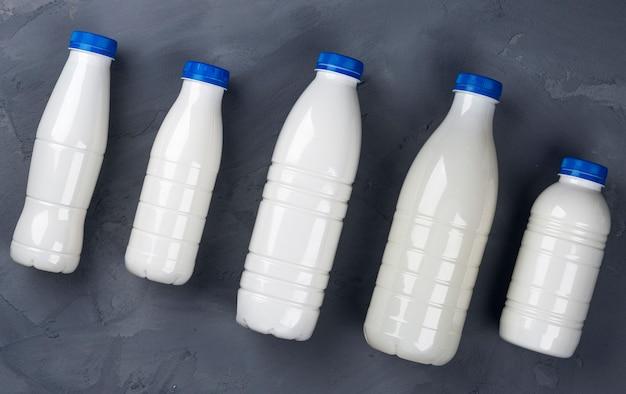 Collezione di bottiglie di latte su pietra grigia