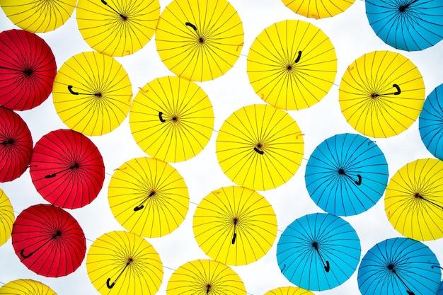 Collezione di ombrelloni multicolori appesi in posizione aperta su una strada che offre ombra e protezione dagli elementi.