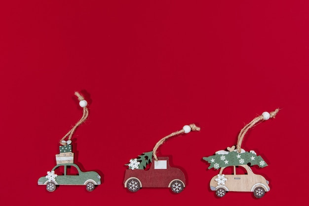 Collezione di macchinine appese per il nuovo anno su un albero di natale su sfondo rosso