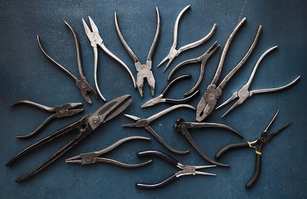Raccolta di vecchi utensili manuali per la lavorazione dei metalli su un tavolo blu ruvido, vista dall'alto