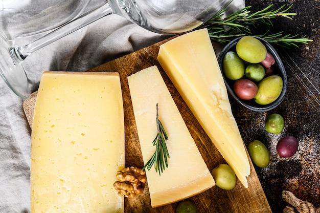 Collezione di formaggi svizzeri, olandesi, francesi, italiani con noci e uva. sfondo scuro vista dall'alto