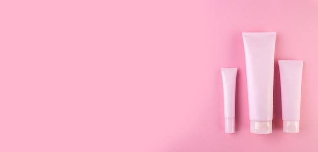 Raccolta di tre tubi cosmetici su sfondo rosa pastello. tubo di plastica con crema per il viso o il corpo in rosa. vista dall'alto, piatto. banner lungo e largo. copia spazio per il tuo design.