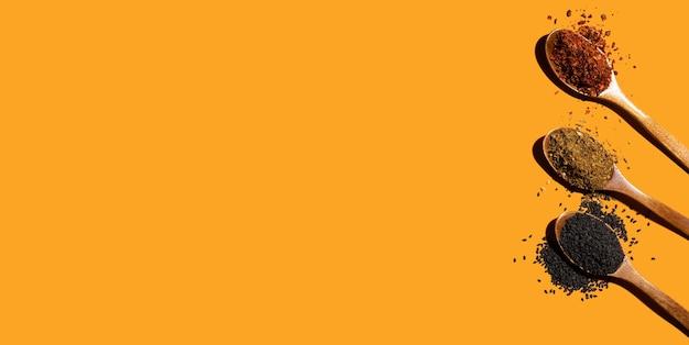 Raccolta di tre spezie su cucchiai di legno su sfondo arancione