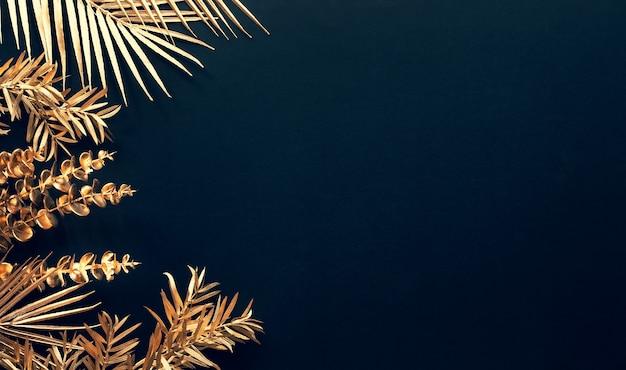 Raccolta di foglie tropicali in colore oro su sfondo nero spazio.decorazione foglia astratta design.arte piatta laici