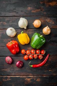 Raccolta di verdure peperone dolce e cipolle, su un vecchio sfondo di tavolo in legno scuro, vista dall'alto piatta