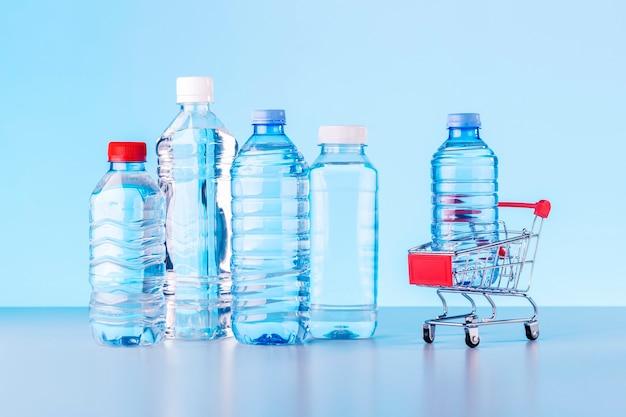 Collezione di bottiglie d'acqua con carrello del negozio su sfondo blu.