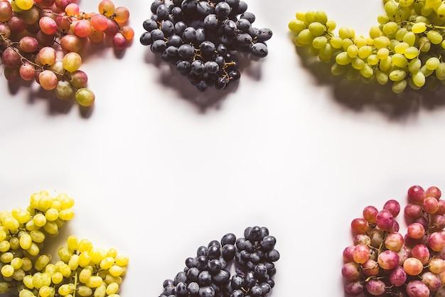 Collezioni di uva matura con foglie isolate su bianco