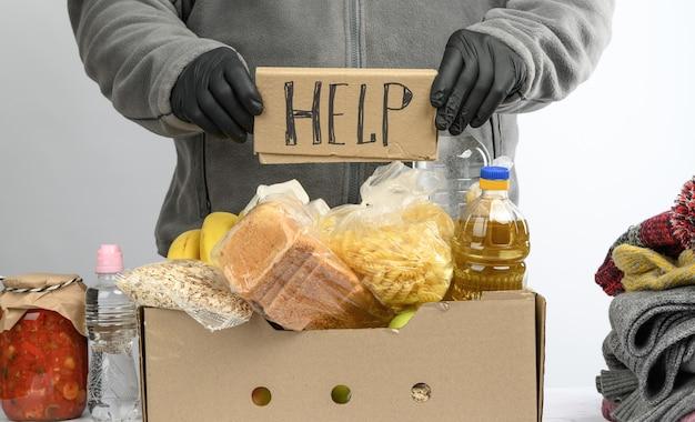 Raccoglie cibo, frutta e cose in una scatola di cartone per aiutare i bisognosi e i poveri, il concetto di aiuto e volontariato