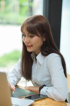 Studentessa universitaria studio sulla classe online dipendente femminile che lavora su tablet con laptop